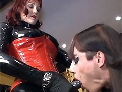 Zoe sucks on a FemDoms strapon cock before teasing a very horny gimp.